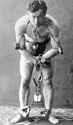 Photo: the escapologist Harry Houdini in chains, c. 1899. Source: McManus-Young Collection; Library of Congress.