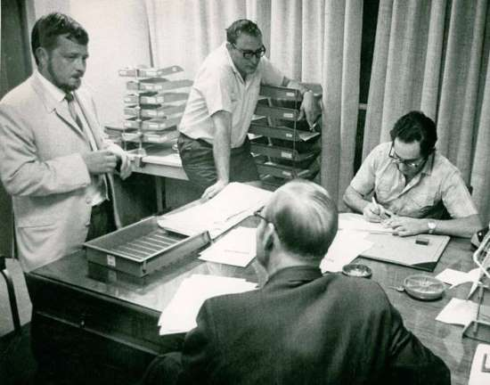 Security Police raid on the Rand Daily Mail. L to R: Rex Gibson, Deputy Editor; Wally Waldeck, Benjamin Pogrund (Night Editor). Policeman has back to camera. Photo courtesy Benjamin Pogrund.